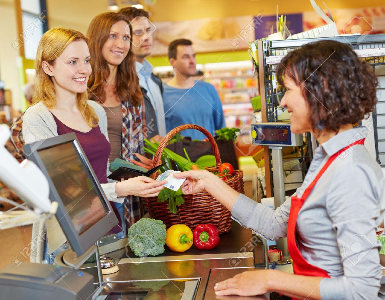 31496700-Mujer-sonriente-que-pagar-en-efectivo-con-Euro-bill-dinero-en-la-caja-del-supermercado-Foto-de-archivo